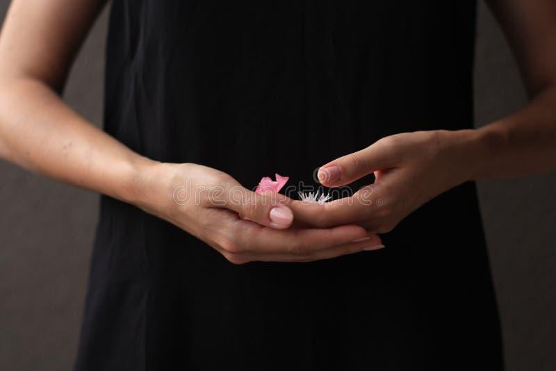 Blommar rosa färger i handen av en kvinna arkivfoton