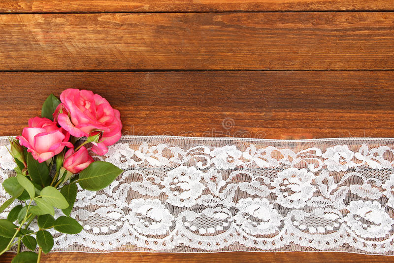 Blommar rosor på en träbakgrund med snör åt arkivbild