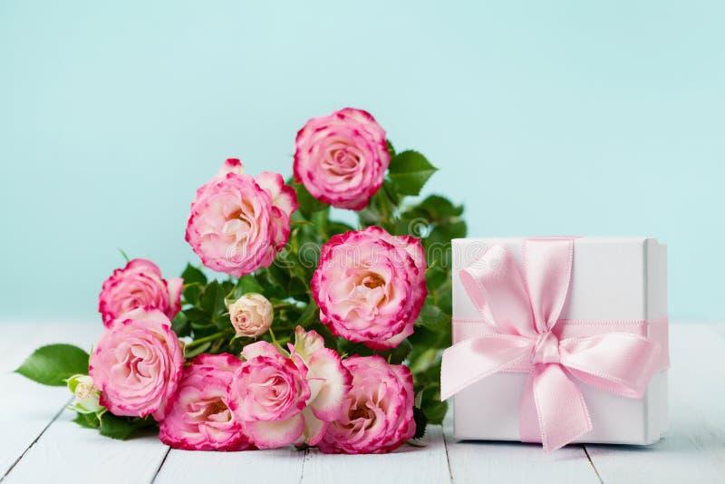 Blommarosor och gåvaask med bandet på tappningtabellen Hälsningkort för födelsedag-, kvinna- eller moderdag Pastellfärgad färg royaltyfria foton
