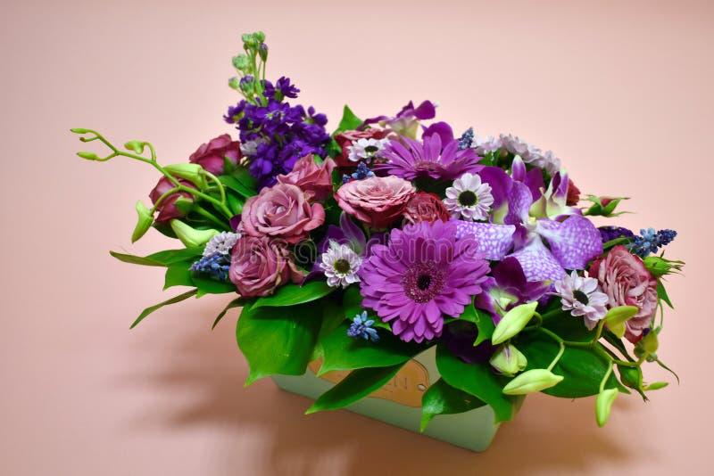Blommasammansättning i original- ask på rosa färger arkivbild