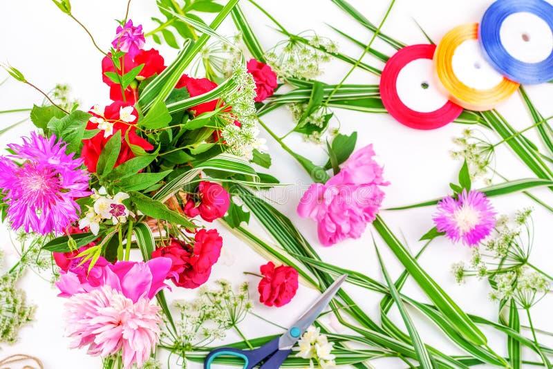Blommasammansättning med en bukett av rosa pionblommor, blåklinter och röda kulöra band för rosor och på en vit bakgrund som är b arkivbild