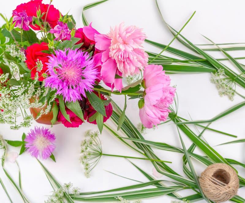 Blommasammansättning med en bukett av rosa pionblommor, blåklinter och röda rosor på en vit bakgrund, bästa sikt royaltyfria bilder