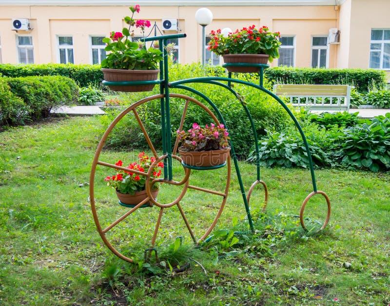 Blommaställningen i parkerar gjorde i form av en cykel arkivfoto
