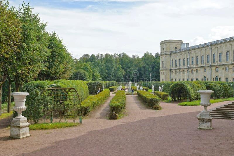 Blommaträdgård med antika statyer i Gatchina royaltyfria foton