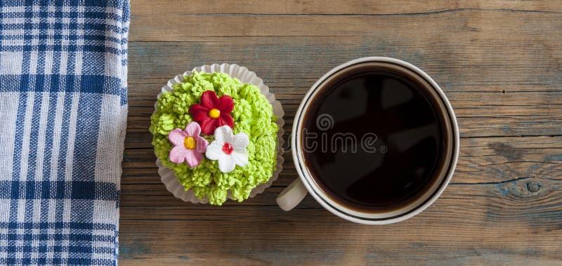 Blommavårmuffin med den varma kaffekoppen på trätabellen royaltyfri foto