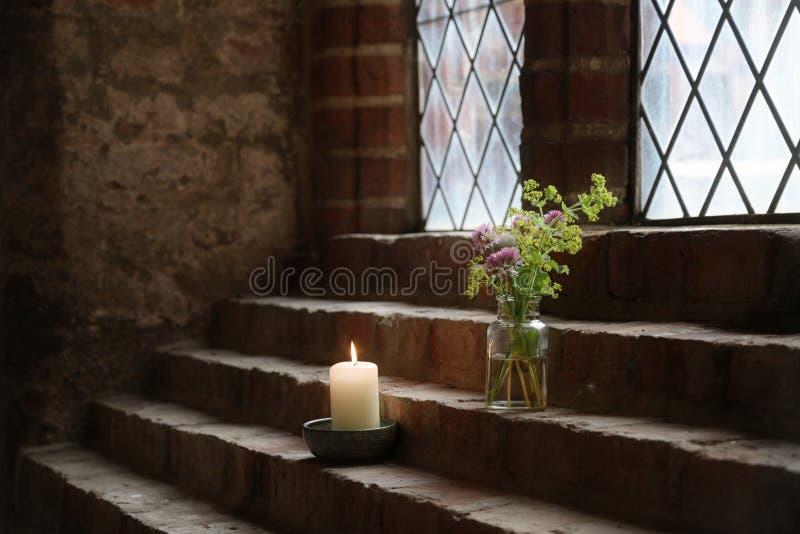 Blommavas och en brinnande stearinljus på tegelstenmoment som garnering på ett ledningsexponeringsglasfönster i en gammal kloster arkivbild