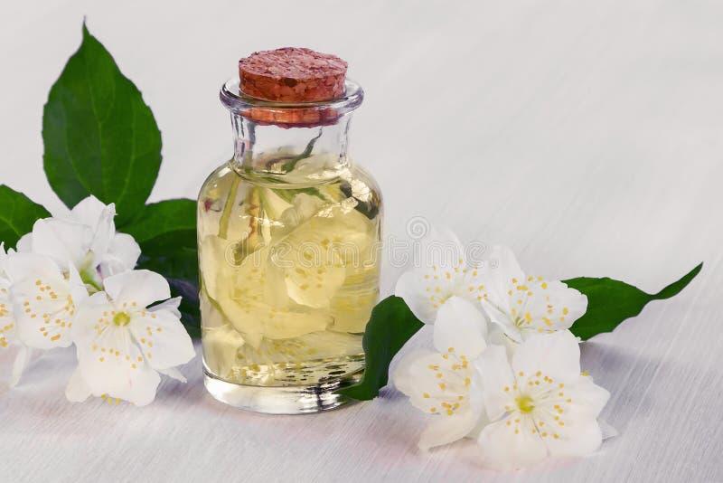 Blommor av philadelphusen någonstans kallade jasmin eller den falska apelsinen och en flaska av olja på en vit trätabell arkivbild