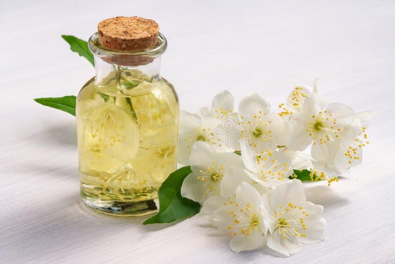 Blommor av philadelphusen någonstans kallade jasmin eller den falska apelsinen och en flaska av olja på en vit trätabell arkivfoto
