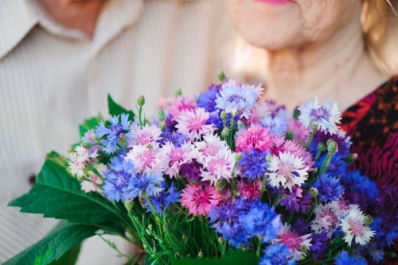 Blommor för en härlig äldre kvinna brudgum för bukettbrudfokus royaltyfria foton