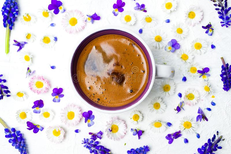 Blommor för kaffekopp och vårpå vita den lekmanna- bakgrundslägenheten arkivfoto