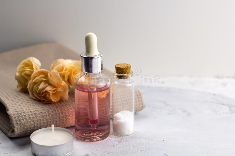Blommor för olje- flaskor för hav för arom nya salta på handdukmarmortabellen arkivbilder