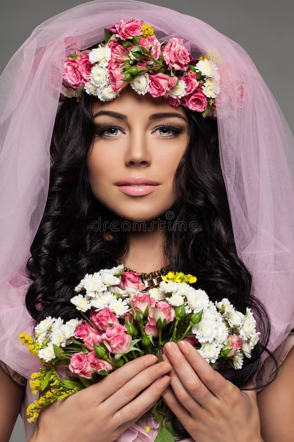 Blommor för sommar för härlig brunettkvinna hållande royaltyfri bild