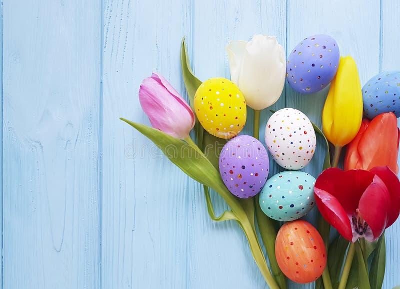 Blommor för tulpan för påskägg som är dekorativa på blå träfestival, mönstrar vår royaltyfri bild