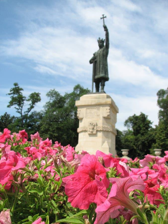 Blommor framme av en Stefan Cel Mare Statue i Moldavien - MOLDAVIEN arkivfoton