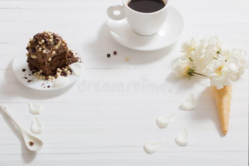 Blommor i dillandekotte och chokladkaka på träbackg royaltyfri foto