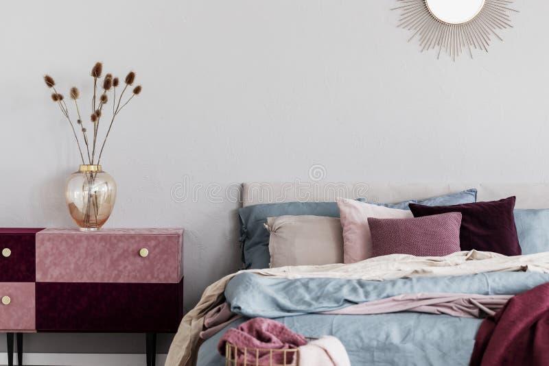 Blommor i elegant exponeringsglasvas på diy sammet täckte pastellfärgad rosa och burgundy nightstand bredvid hemtrevlig säng med  arkivbilder