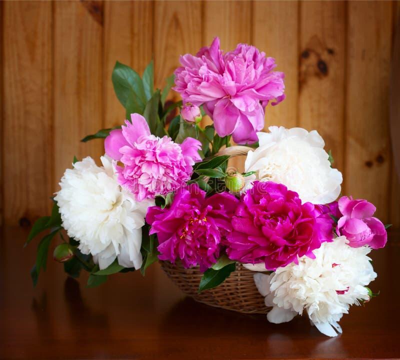 Blommor i en vas på den gamla trätabellen royaltyfri fotografi