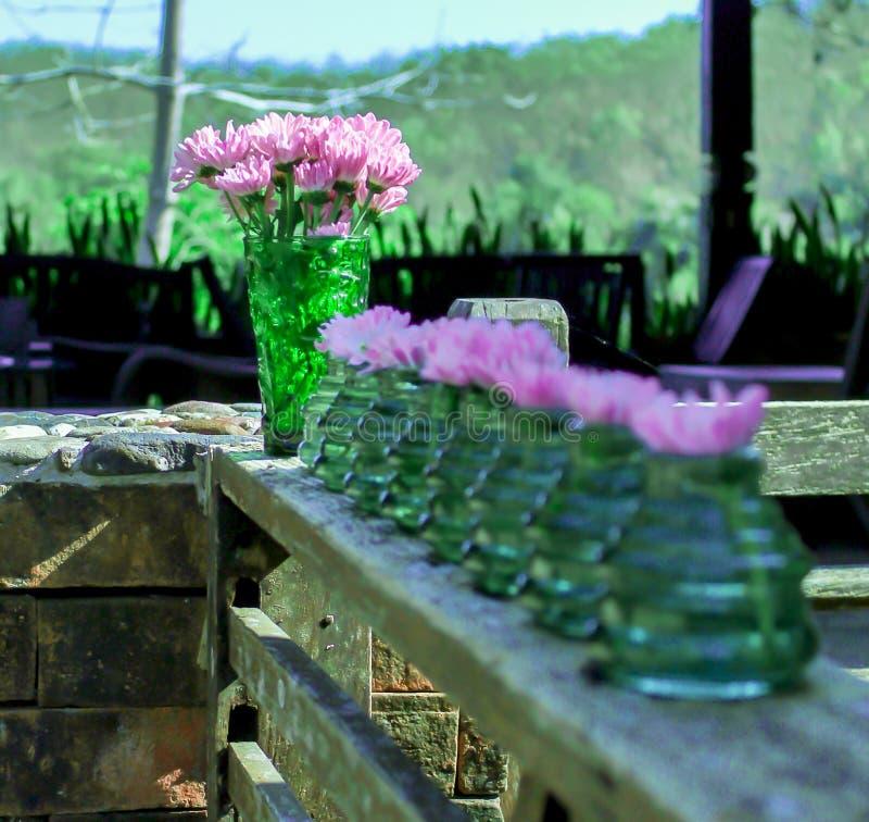 Blommor i en vas på en träbalkong royaltyfria bilder
