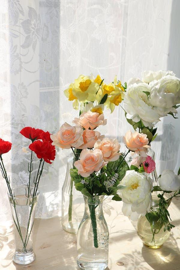 Blommor i en vas p? ett soligt f?nster i ett lantligt hus p? en tr?tabell arkivbilder