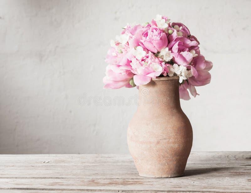 Blommor i gammal tillbringare royaltyfri bild