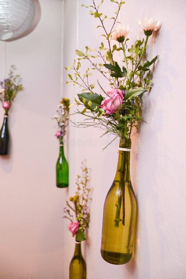 Blommor i hängande flaskor royaltyfri foto
