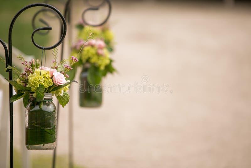 Blommor i murarekrus på bröllopceremoni arkivfoto