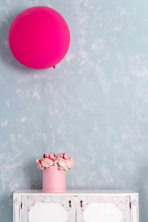 Blommor i rund lyxgåva boxas, och stora rosa färger sväller på byrå Bukett av rosa och vita pioner i papper royaltyfria foton