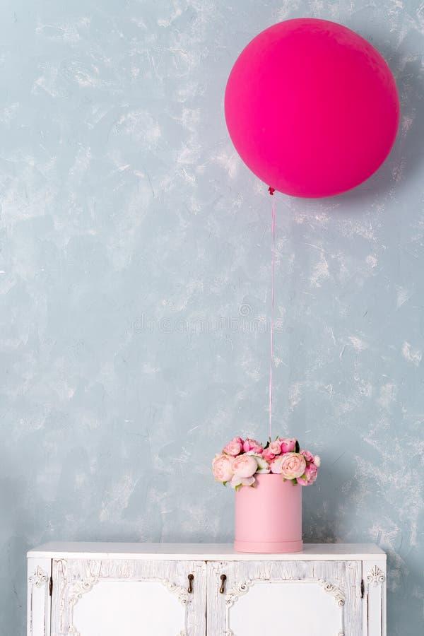 Blommor i rund lyxgåva boxas, och stora rosa färger sväller på byrå Bukett av rosa och vita pioner i papper royaltyfria bilder