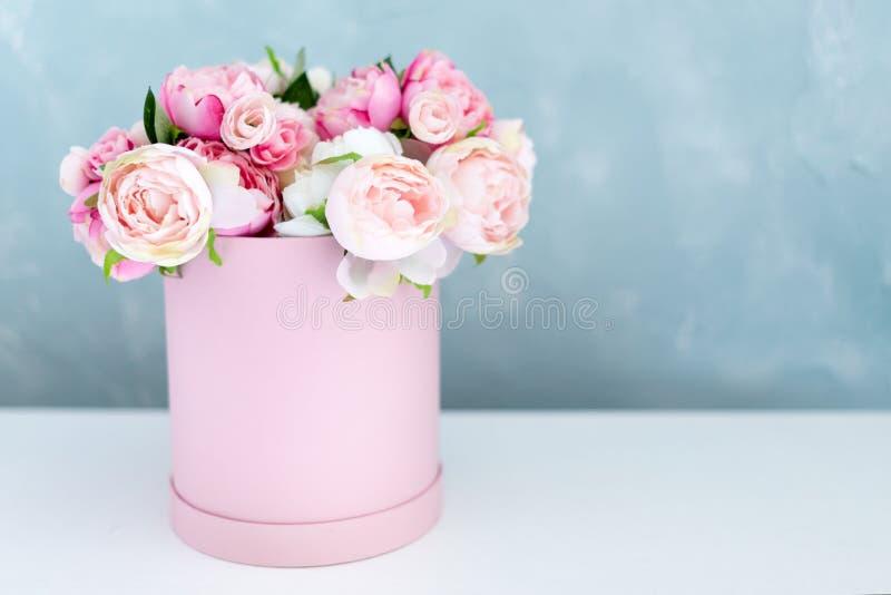Blommor i rund lyxgåvaask Bukett av rosa och vita pioner i pappers- ask Modell av hattasken av blommor med arkivfoto