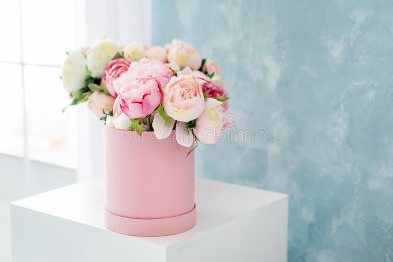 Blommor i rund lyxgåvaask Bukett av rosa och vita pioner i pappers- ask nära fönstret Modell av hattasken royaltyfri foto