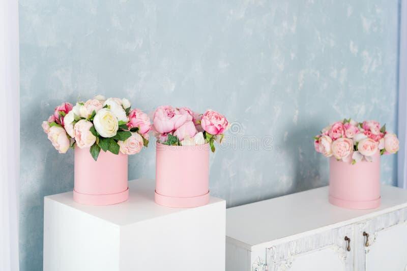 Blommor i runda lyxgåvaaskar Bukett av rosa och vita pioner i pappers- ask Modell av hattasken av blommor arkivbilder