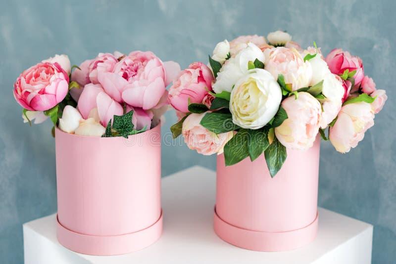 Blommor i runda lyxgåvaaskar Bukett av rosa och vita pioner i pappers- ask Modell av hattasken av blommor royaltyfri foto