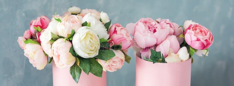Blommor i runda lyxgåvaaskar Bukett av rosa och vita pioner i pappers- ask Modell av hattasken av blommor royaltyfria foton