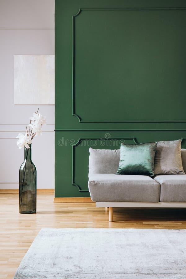 Blommor i stor grön flaskform som vasen bredvid grå soffa i trendig vardagsruminre royaltyfri fotografi