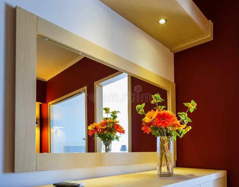 Blommor i vas på spegeln på tabellen i den moderna vardagsrummet arkivbild
