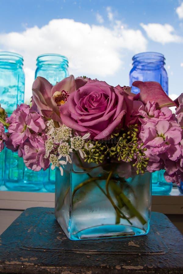 Blommor och exponeringsglaskrus royaltyfri foto