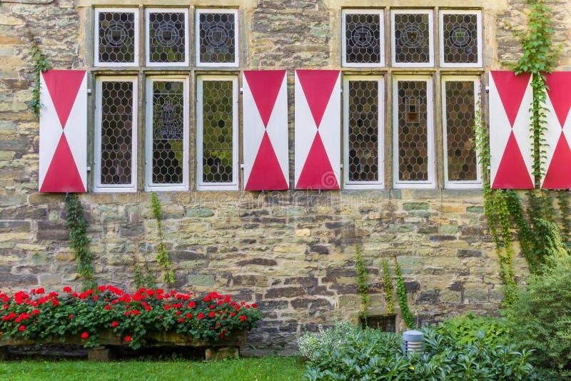 Blommor och fönster av det Burghof museet i Soest arkivbild