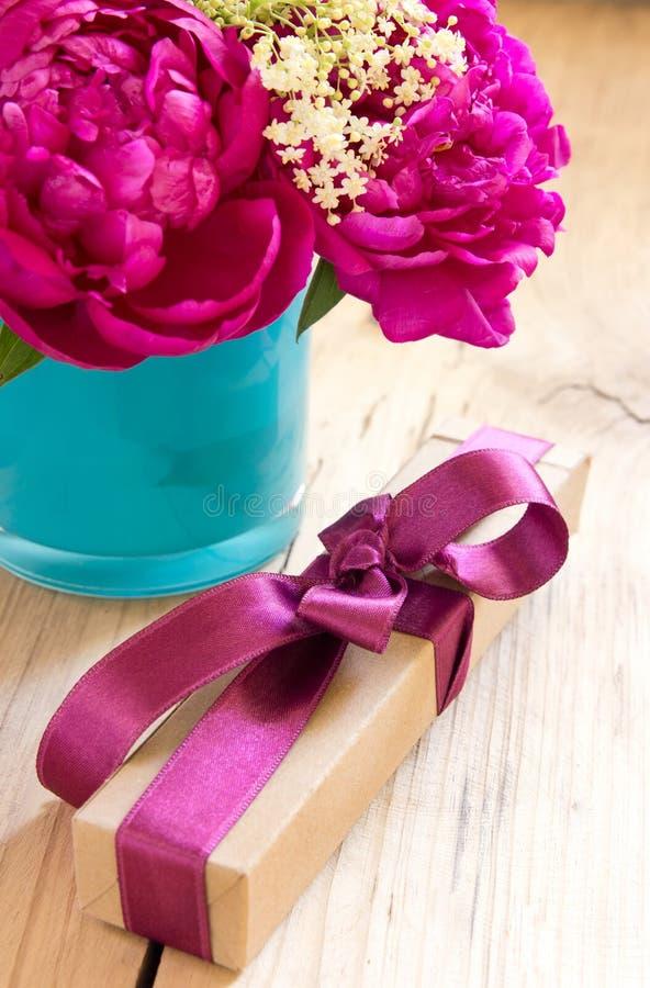 Blommor och gåva boxas med bandet på tabellen, födelsedaggåva arkivbilder