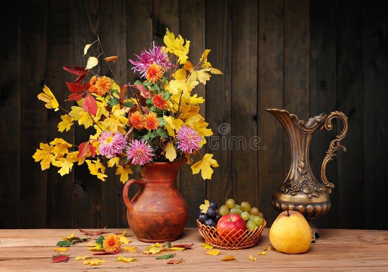 Blommor och sidor i en metalltillbringare och frukt arkivbild