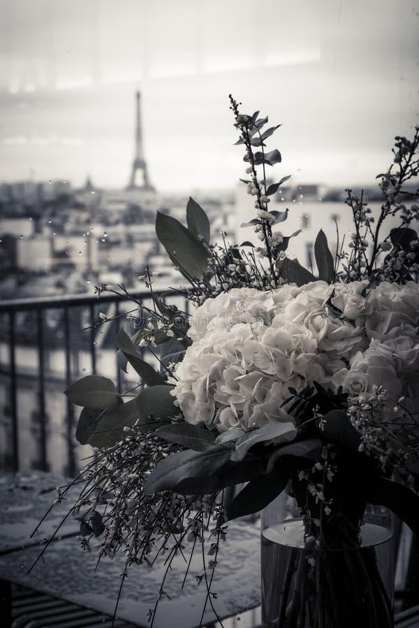 Blommor på balkong med stadssikt till Eiffeltorn royaltyfri bild