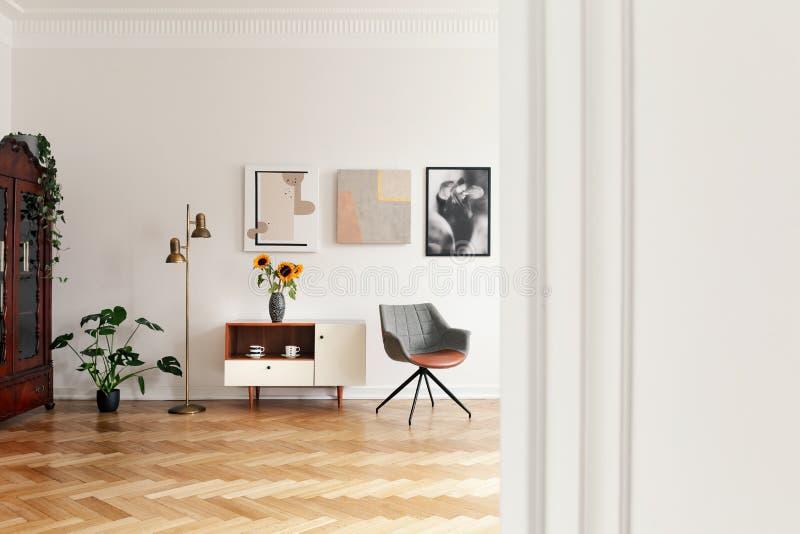 Blommor på skåp mellan den guld- lampan och grå färgstol i den vita lägenhetinre med växten Verkligt foto arkivbilder