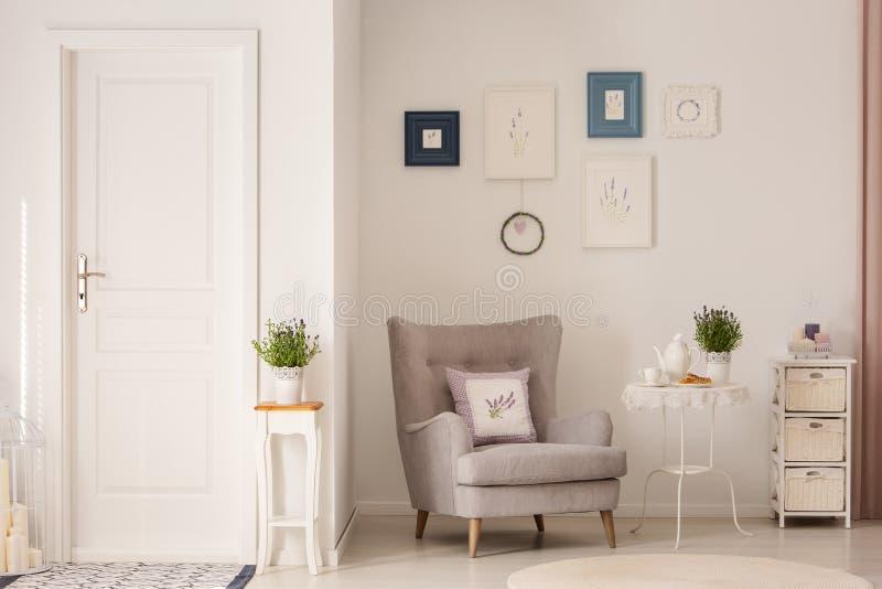 Blommor på tabellen bredvid den gråa fåtöljen i den vita vardagsruminre med affischer och dörren Verkligt foto royaltyfria bilder
