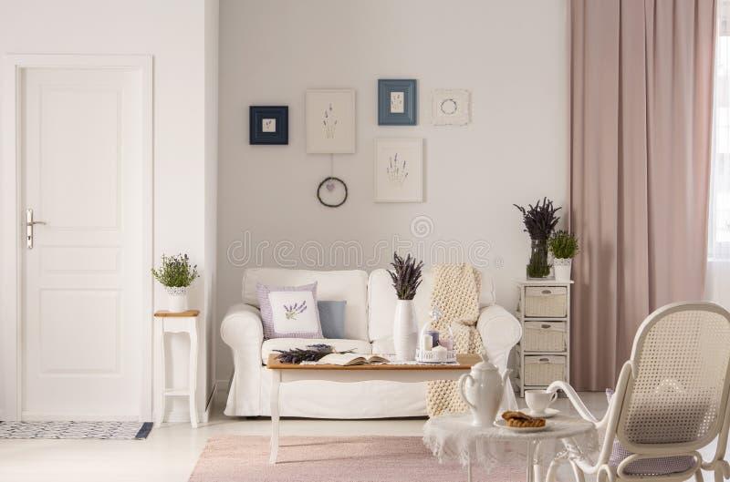 Blommor på tabellen framme av den vita soffan i rosa vardagsruminre med dörren och fåtöljen Verkligt foto royaltyfria foton