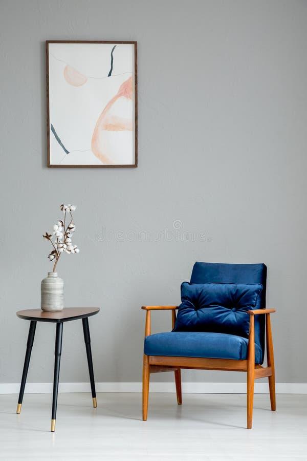 Blommor på trätabellen bredvid den blåa fåtöljen i grå lägenhetinre med affischen royaltyfri foto