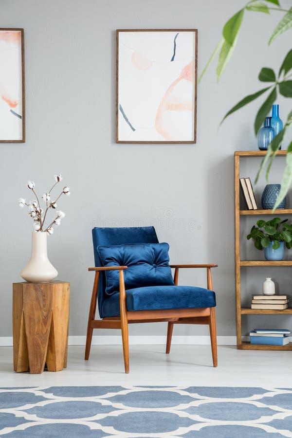 Blommor på trätabellen bredvid den blåa fåtöljen i grå vardagsruminre med affischer arkivfoto