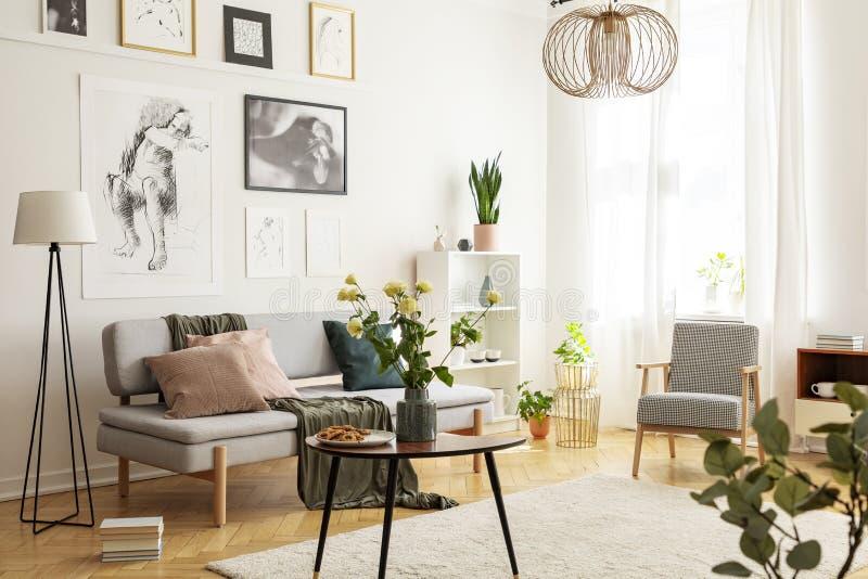 Blommor på trätabellen bredvid den gråa soffan i vardagsrum som är inre med lampan och affischer Verkligt foto royaltyfria foton