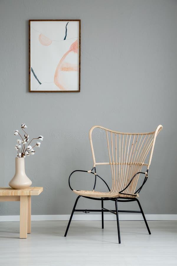 Blommor på trätabellen bredvid den moderna fåtöljen i grå lägenhetinre med affischen Verkligt foto fotografering för bildbyråer