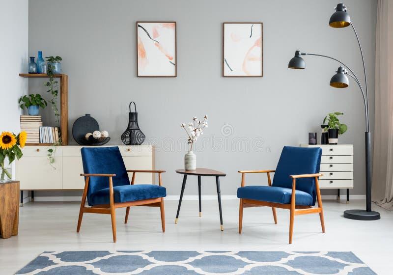 Blommor på trätabellen mellan blåa fåtöljer i vardagsruminre med affischer Verkligt foto arkivbild