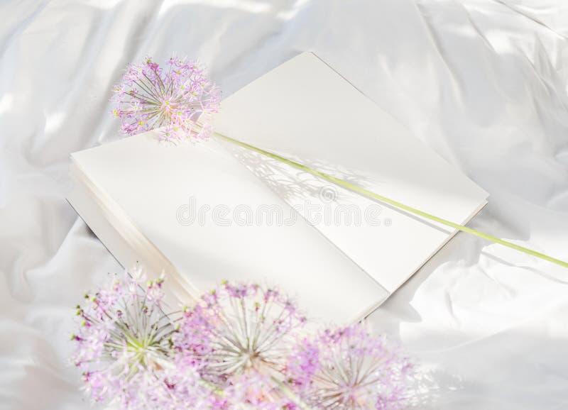 Blommor som blir på den öppna boken i säng Romantisk bra morgon Top besk?dar royaltyfri fotografi