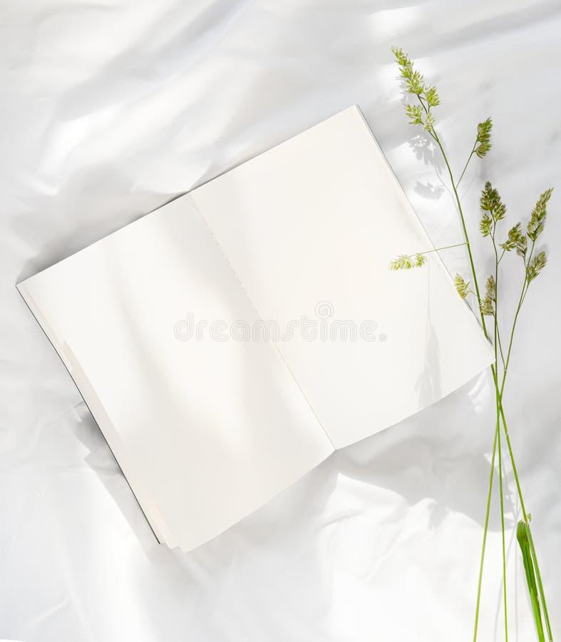 Blommor som blir på den öppna boken i säng Romantisk bra morgon Top besk?dar royaltyfria bilder
